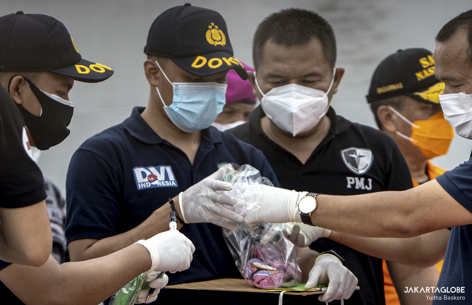 Police Disaster Victim Identification team at the Tanjung Priok post identifid girl t-shirt suspected coming from the Boeing 737-524 plane at JICT 2, Port of Tanjung Priok, in North Jakarta on Saturday (10/01). (JG Photo/Yudha Baskoro)
