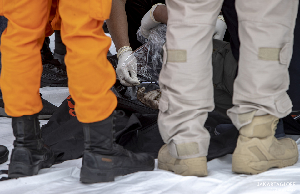 National Police Disaster Victims Identification inspect a body part of a Boeing 737-500 crash victims at the Tanjung Priok in North Jakarta on Jan, 10, 2021. (JG Photo/Yudha Baskoro)