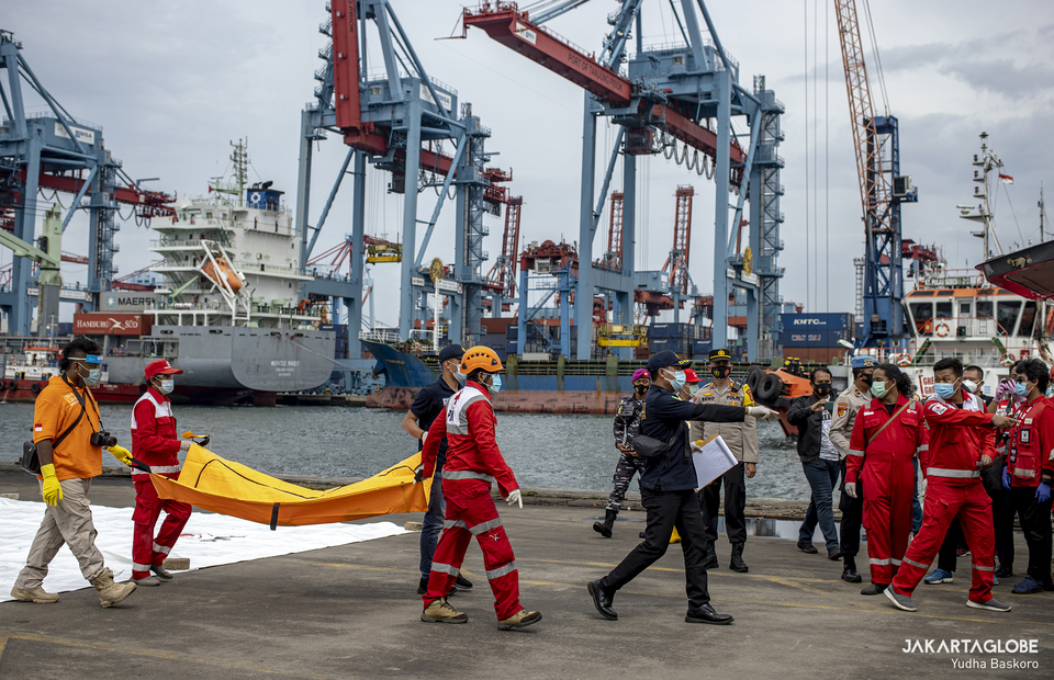 Indonesian Red Cross Personnels carry a body bag to a hearse at the Tanjung Priok in North Jakarta on Jan, 10, 2021. (JG Photo/Yudha Baskoro)