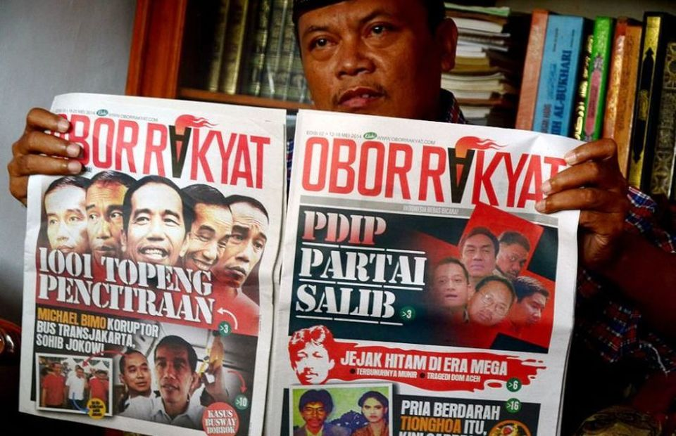 A man shows two copies of Obor Rakyat tabloid in Tegal, Central Java, on July 6, 2014. The tabloid was published as a smear campaigh agaist presidential candidate Joko Widodo and distributed among Islamic boarding schools in East and Central Java. (Antara Photo/Oky Lukmansyah)