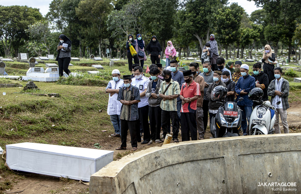 Relatives of the deceased perform the traditional Islamic prayer for the dead at Srengseng Sawah public cemetery in South Jakarta on Tuesday (26/01). (JG Photo/Yudha Baskoro)