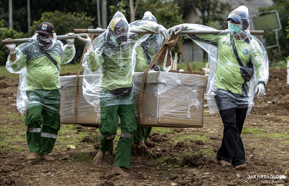 Funeral service workers wearing protective gear carry the coffin of suspect Covid-19 victims at Srengseng Sawah public cemetery in South Jakarta on Tuesday (26/01). (JG Photo/Yudha Baskoro)