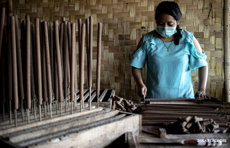 A worker cuts hio before make them dry under the sun at a home industry in Tangerang on Feb, 1, 2021. (JG Photo/Yudha Baskoro)
