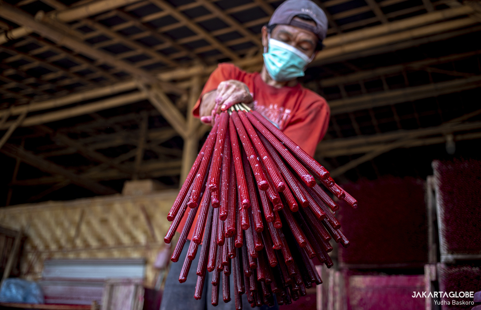 A worker carries some red painted incenses at a home industry in Tangerang on Feb, 1, 2021. (JG Photo/Yudha Baskoro)