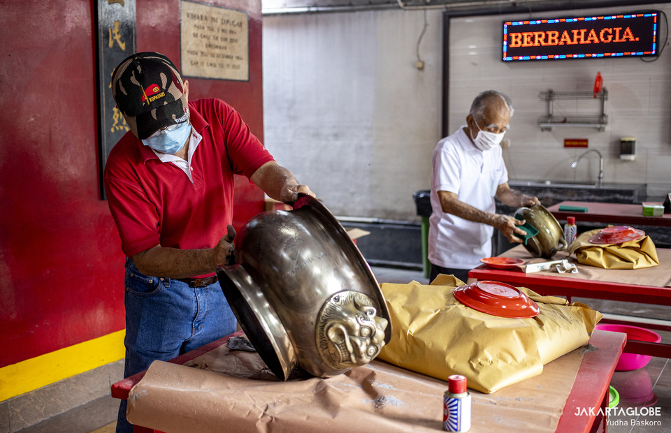 Two man clean pots at Armurva Bhumi Temple (Hok Tek Tjeng Sin) at Karet Semanggi, in South Jakarta, on Feb, 4, 2021 in preparation for Chinese New Year. (JG Photo/Yudha Baskoro)