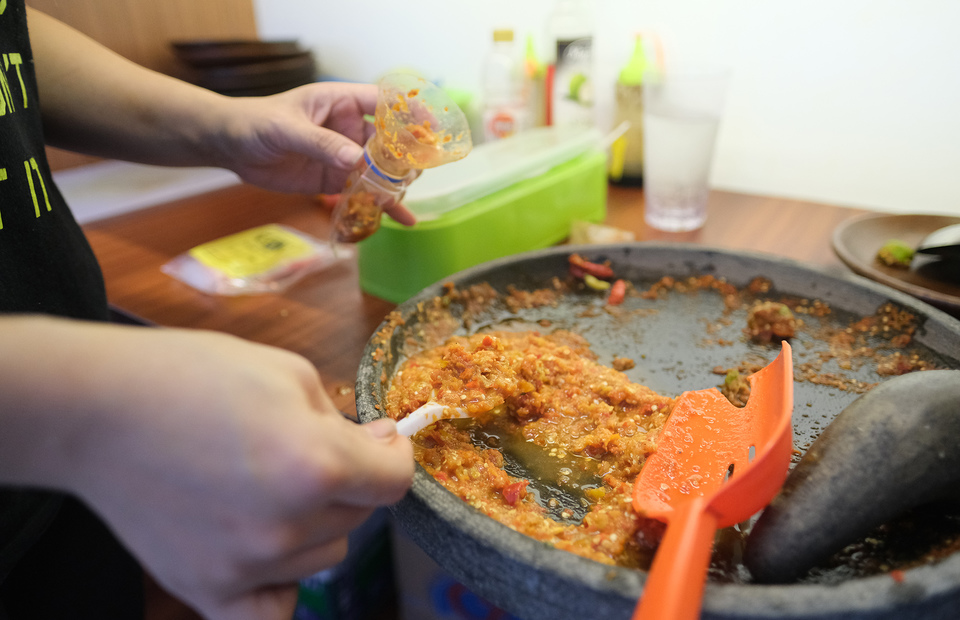 Sego Sambal Cak Brewok founder Cieny makes a spicy chili paste with a mortar and pestle. (Photo Courtesy of Grab)