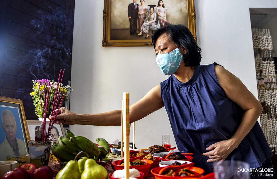 Mrs. Meta puts incense in front of a portrait of her late father after pray at South Tangerang, Banten on Feb 11, 2021. (JG Photo/Yudha Baskoro)