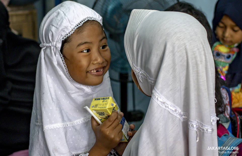 A student smiles as she gets reward during class at Rumah Belajar Merah Putih in Kojem, North Jakarta on Feb 19, 2021. (JG Photo/Yudha Baskoro)