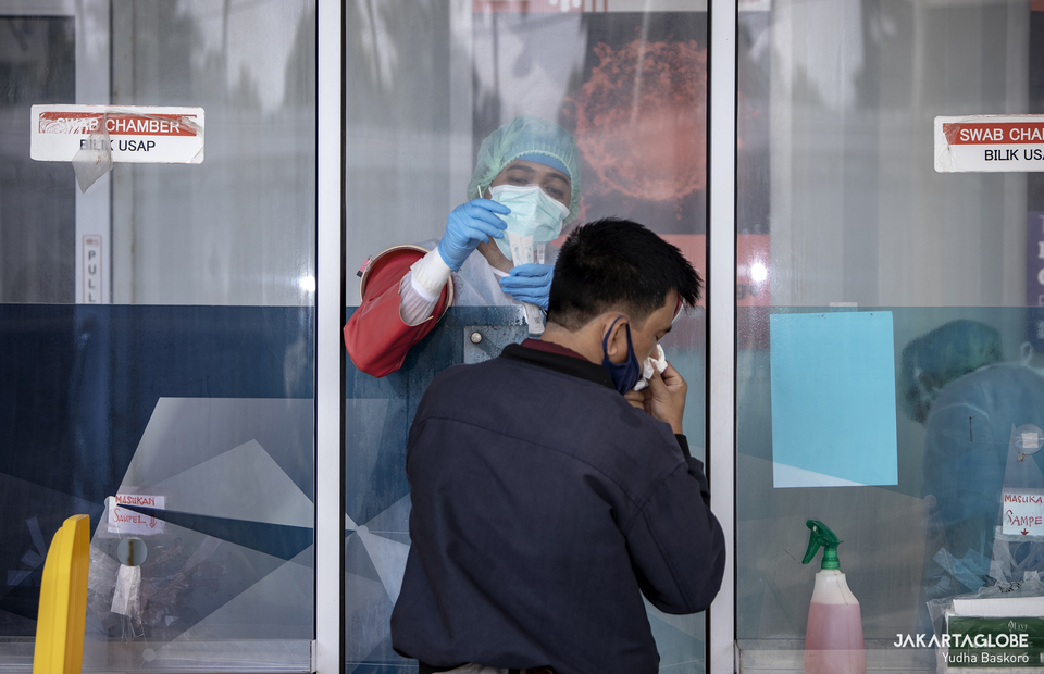 A health worker inside a swab test chamber takes a swab from a man during a Covid-19 PCR test at the GSI Lab in Cilandak, South Jakarta on Feb 23, 2021. (JG Photo/Yudha Baskoro)