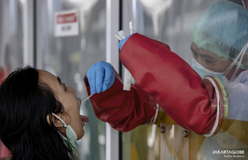 A health worker inside a swab test chamber takes a swab from a woman during a Covid-19 PCR test at the GSI Lab in Cilandak, South Jakarta on Feb 23, 2021. (JG Photo/Yudha Baskoro)