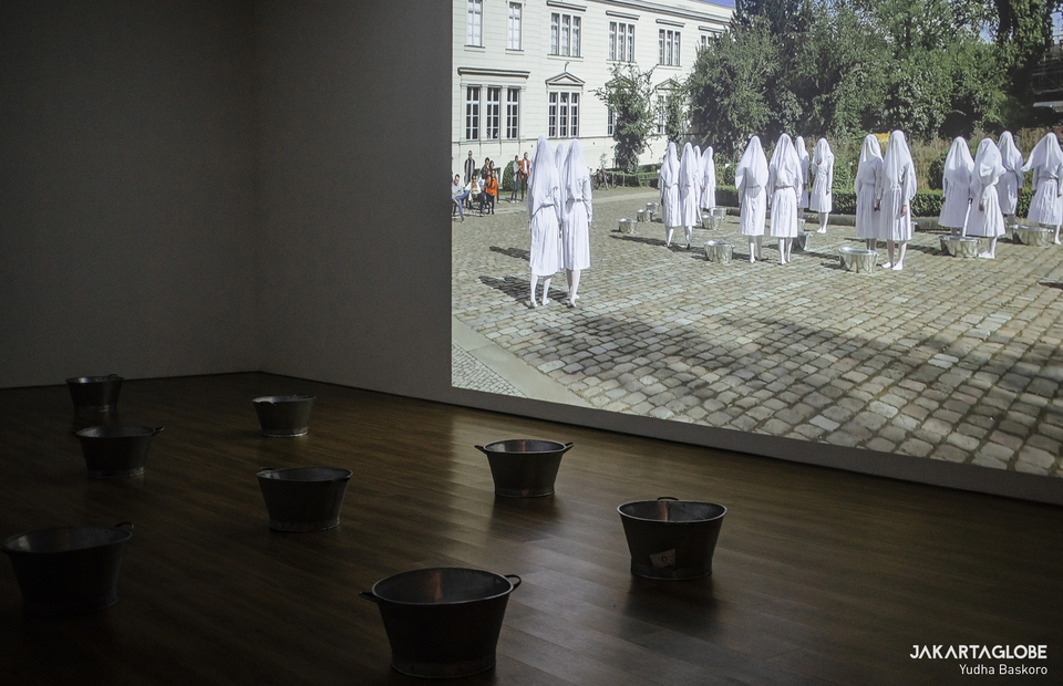 A video shows a performance art of thirty female performers wear white uniforms that obscure their faces for Melati Suryodarmo