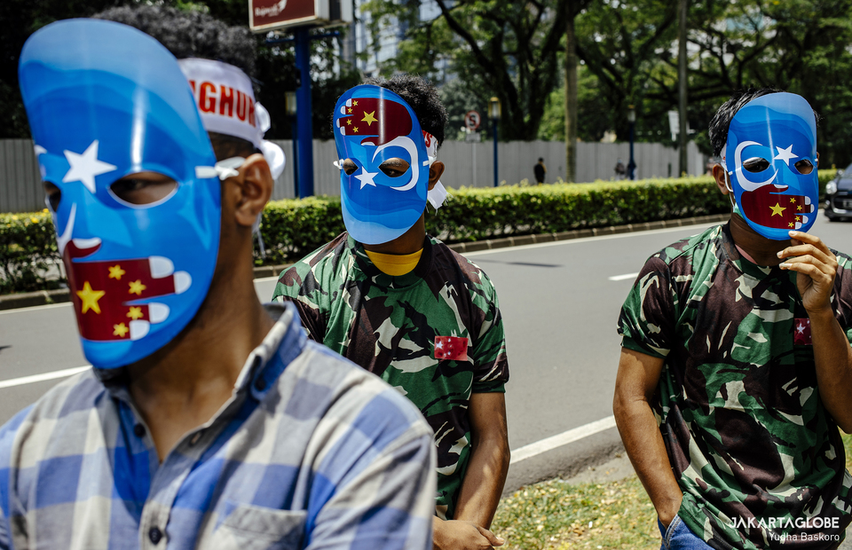 Protesters wearing a mask during protest in front of Embassy of the People
