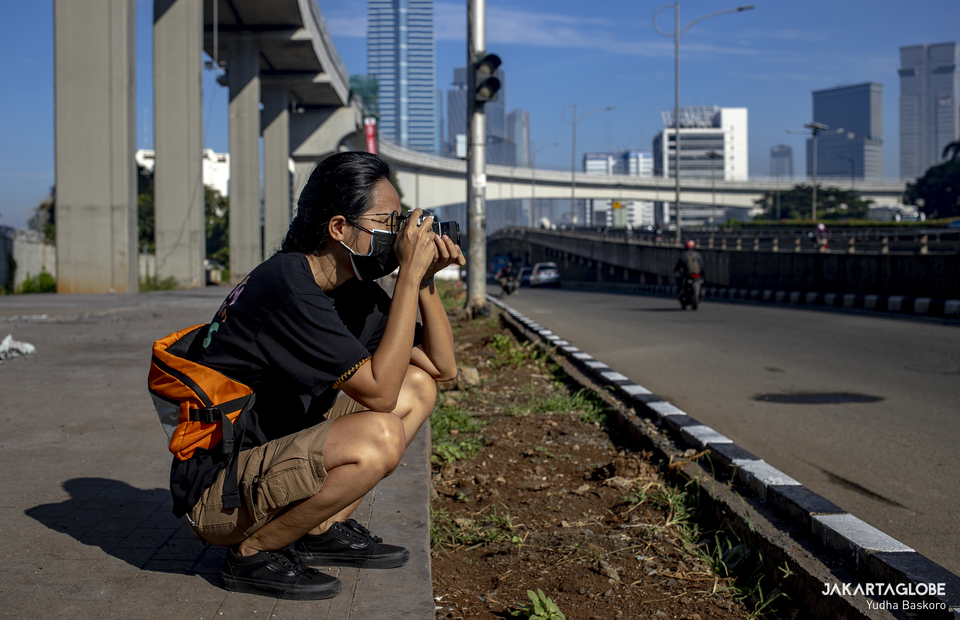 A woman takes a photo using a film camera at Jalan Jend. Gatot Subroto in South Jakarta on March 28, 2021. (JG Photo/Yudha Baskoro)