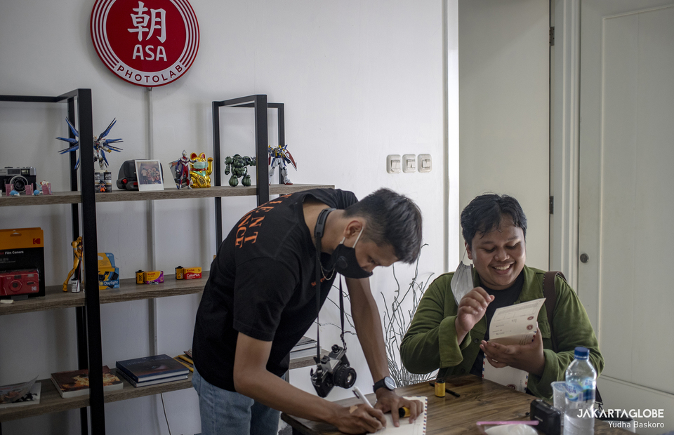 Two young film photographers are seen inside ASA Photolab, a film photo developing and scanning service in Tebet, South Jakarta on March 28, 2021. (JG Photo/Yudha Baskoro)
