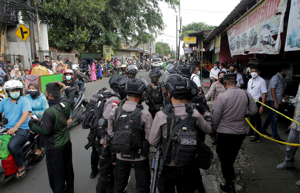 Jakarta Police officers stand guard near a house in Condet, East Jakarta, on March 29, 2021. Police raided the house and discovered explosive materials weighing 1.5 kilograms. (Beritasatu Photo/Joanito De Saojoao)