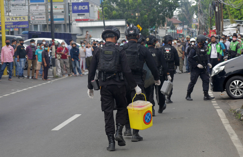 Jakarta Police officers leave the scene after a counter-terror raid at a house in Condet, East Jakarta, on March 29, 2021. (Beritasatu Photo/Joanito De Saojoao)