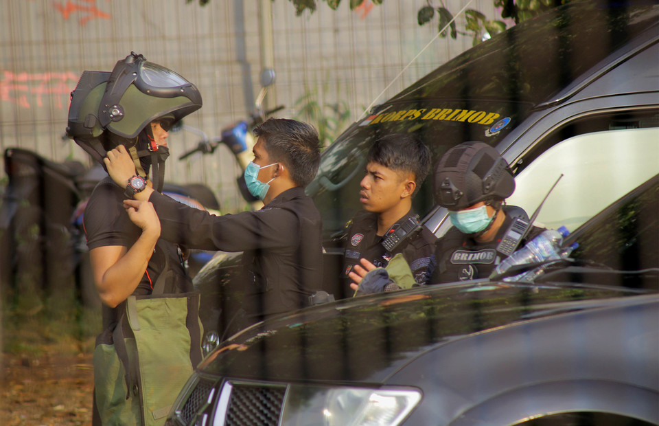 Jakarta Police bomb squad members prepare themselves to neutralize suspected explosive devices found during a raid at a house in Condet, East Jakarta, on March 29, 2021. (Beritasatu Photo/Joanito De Saojoao)