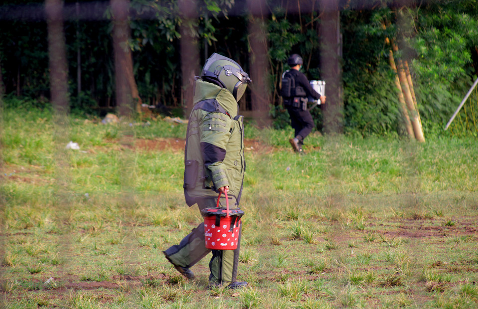 A bomb squad member in protective suit carries suspected explosive devices for a controlled explosion at a safe area in Condet, East Jakarta, on March 29, 2021. (Beritasatu Photo/Joanito De Saojoao)