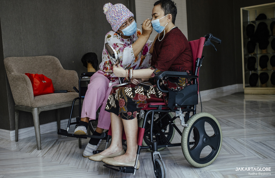 Rina Paays helps a cancer survivor, Riana Trish wearing make up as they choose wig at Sasana Marsudi Husada in South Jakarta on March 30, 2021. (JG Photo/Yudha Baskoro)