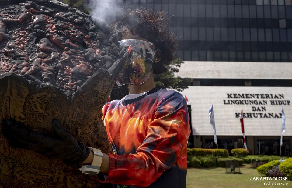 An environmental activist performs a theatrical act during protest in front of the Environment and Forestry Ministry (KLHK) building in Central Jakarta on April 8, 2021. (JG Photo/Yudha Baskoro)