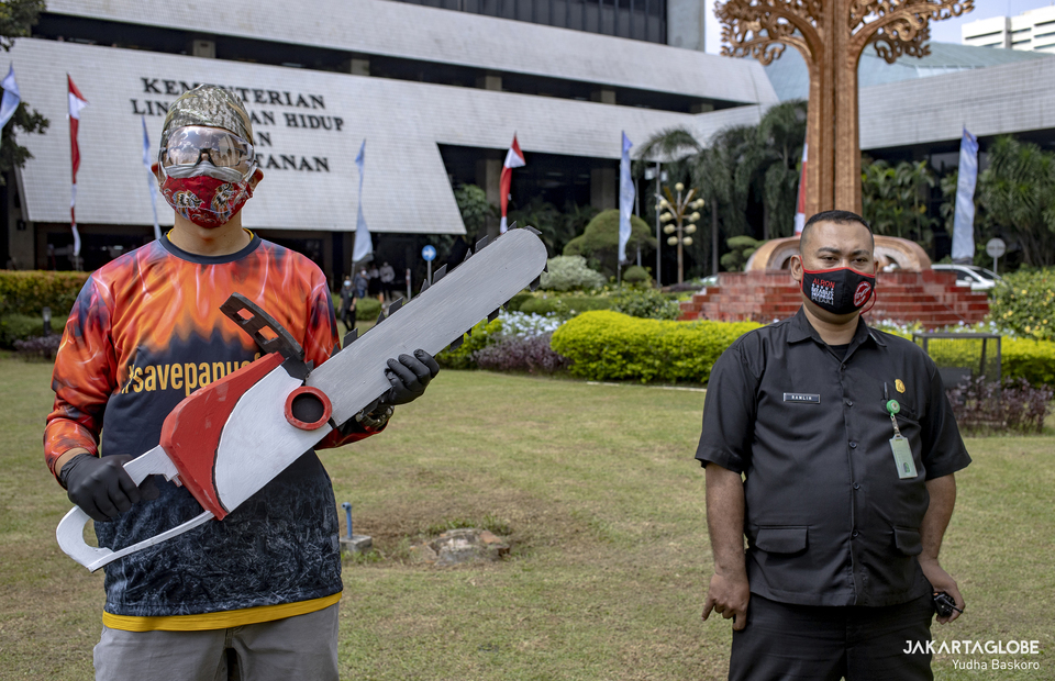 A protesters carries a chainsaw replica as he stands beside a security personnel during protest in front of the Environment and Forestry Ministry (KLHK) building in Central Jakarta on April 8, 2021. (JG Photo/Yudha Baskoro)