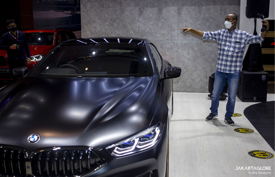 Indonesian former racer Fitra Eri takes a video beside a BMW 8 Series luxury sports car Golden Thunder Edition during Indonesia International Motor Show (IIMS) Hybrid 2021 at JIexpo Kemayoran in Central Jakarta on April 15, 2021. (JG Photo/Yudha Baskoro)