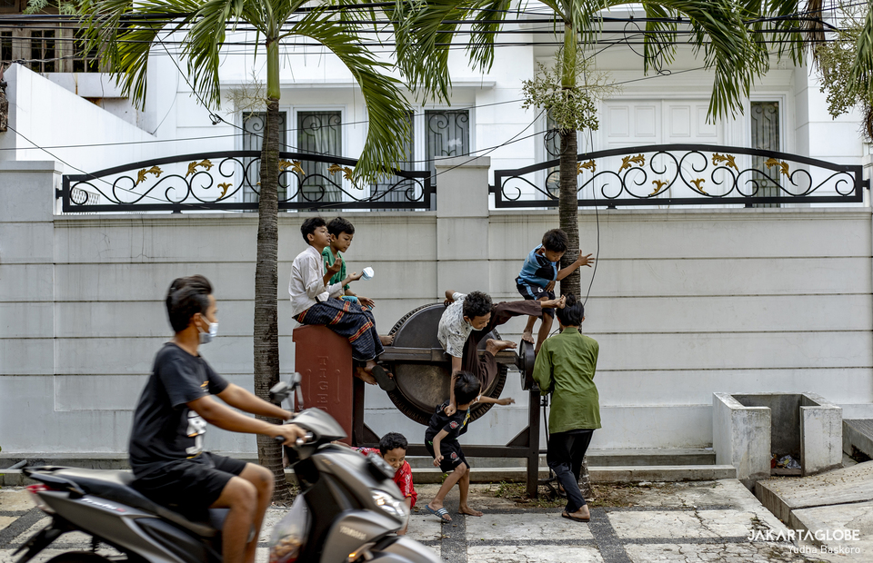 Children fall from cement mixer as they waiting for the free iftar meal in Cempaka Putih, Central Jakarta, on April 19, 2021. (JG Photo/Yudha Baskoro)