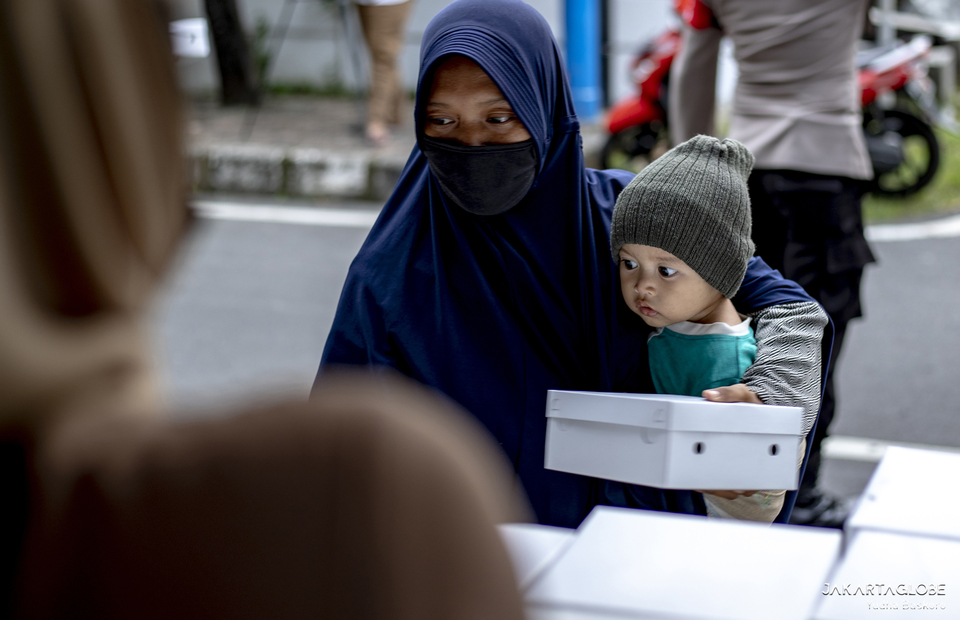 A child reacts as his mother receives a free iftar meal in Cempaka Putih, Central Jakarta, on April 19, 2021. (JG Photo/Yudha Baskoro)