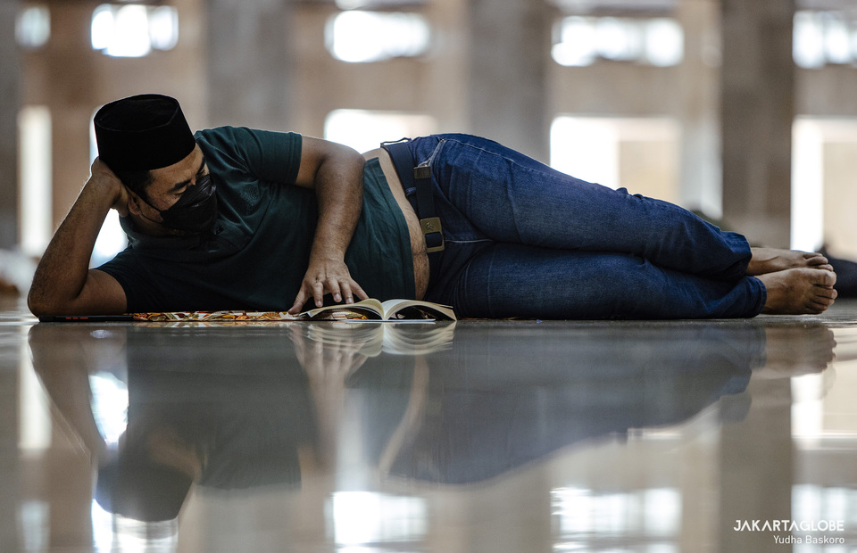A man reads religious book after Friday prayer at Istiqlal Mosque in Central Jakarta on April 23, 2021. (JG Photo/Yudha Baskoro)