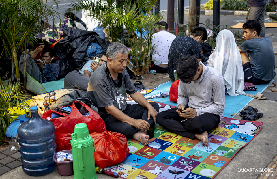 Refugees and asylum seekers from Afghanistan stranded on a sidewalk outside the offices of the United Nations High Commissioner for Refugees (UNHCR) in Central Jakarta on April 27, 2021. (JG Photo/Yudha Baskoro)