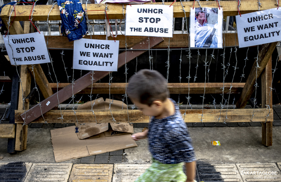 A child runs in front of police barbed wire outside the offices of the United Nations High Commissioner for Refugees (UNHCR) in Central Jakarta on April 27, 2021. (JG Photo/Yudha Baskoro)