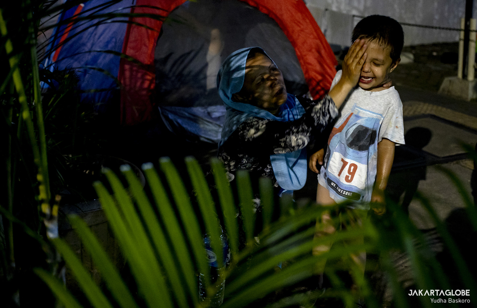A mother cleans her son face before sleep outside the offices of the United Nations High Commissioner for Refugees (UNHCR) in Central Jakarta on April 27, 2021. (JG Photo/Yudha Baskoro)