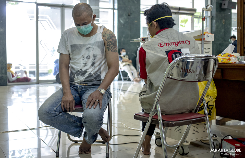 A man removes his colored-tattoo at the Assahara Mosque inside the West Jakarta Mayor