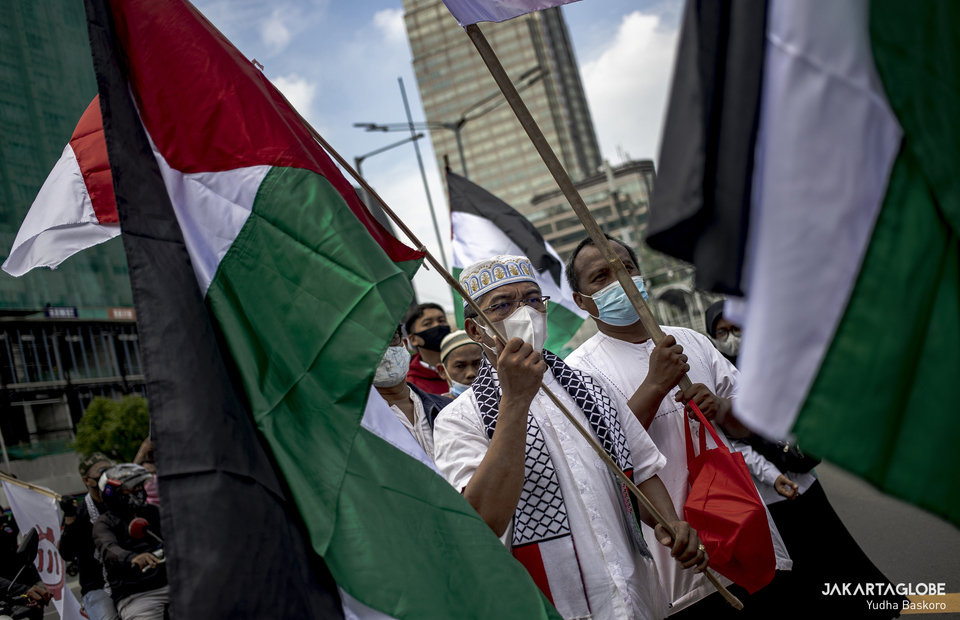 Protesters carry Palistinian flag during protest against Israel at Jalan M.H Thamrin in Central Jakarta on May 18, 2021. (JG Photo/Yudha Baskoro)