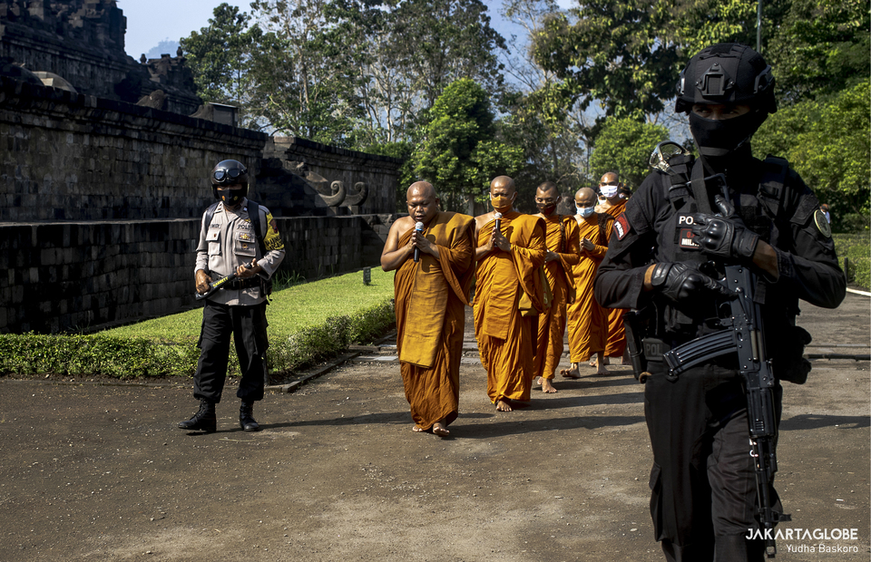 Indonesian police personnels escort Buddhist monks, followed by devotees, participate in a pradakshina ritual during Vesak celebration at the Borobudur Temple in Central Java, on May 26, 2021. (JG Photo/Yudha Baskoro)