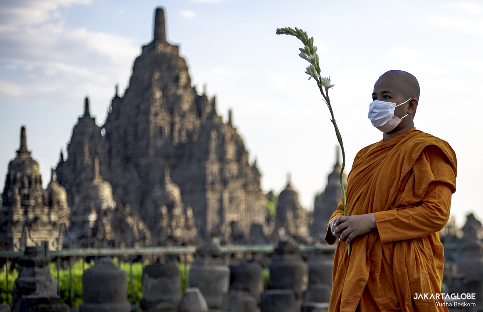A buddhist monk carries flower during pradakshina ritual at the Sewu Temple in Central Java, on May 26, 2021. (JG Photo/Yudha Baskoro)