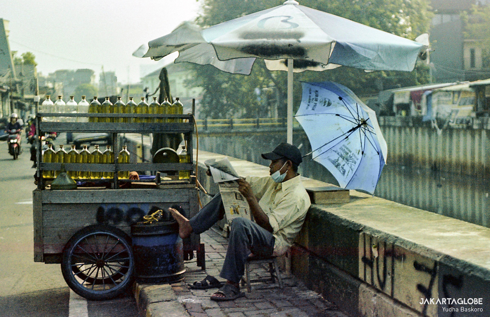 Photo taken with film camera - A gas trader sits as he reads a morning newspaper at Tambora area in Central Jakarta on June 3, 2021. (JG Photo/Yudha Baskoro)
