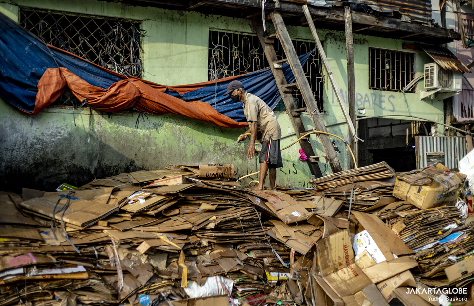 A man cleans up some pile of cardboard at Tambora area in Central Jakarta on June 3, 2021. (JG Photo/Yudha Baskoro)
