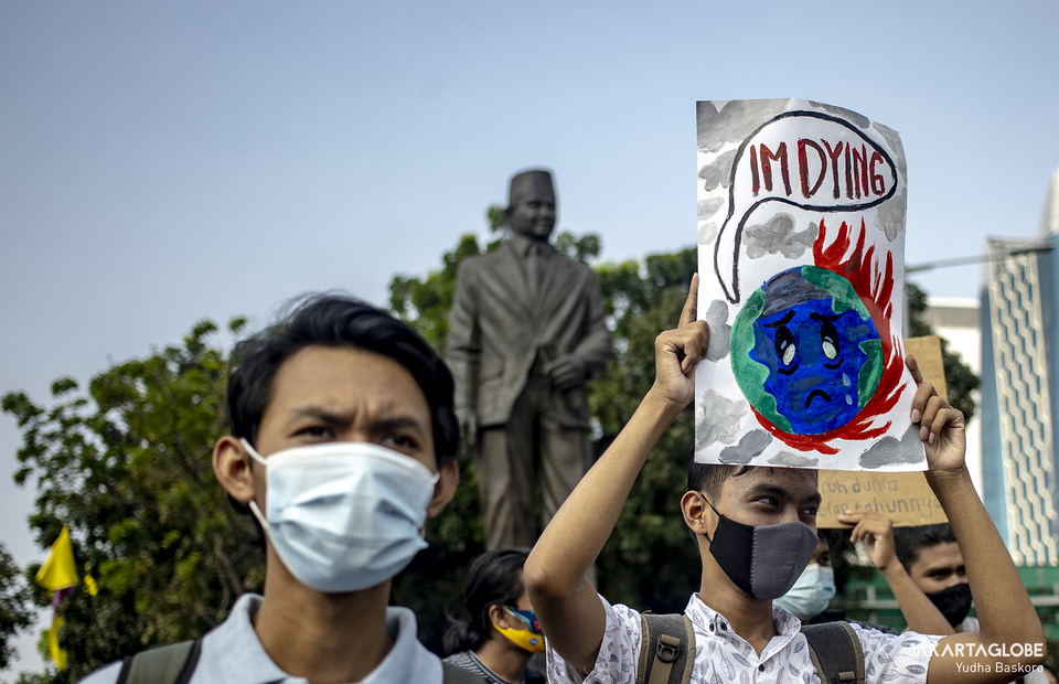 Activist carries a placard in front of M.H. Thamrin statue in Central Jakarta during protest against climate crisis on June 4, 2021. (JG Photo/Yudha Baskoro)