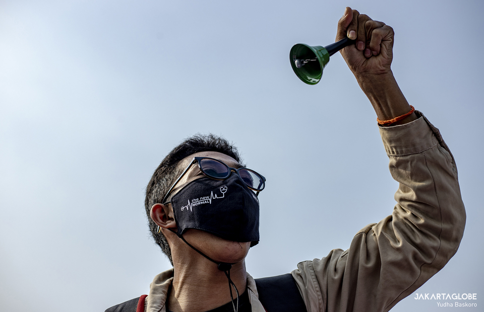 A protester ring a bell as a symbolic statement of that Indonesia is currently in a