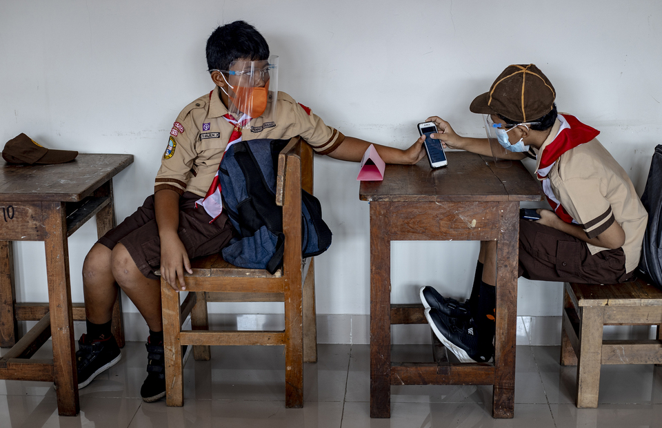 A student helps his friend during Jakartas second phase of school reopening program at Cideng 10 Elementary School in Central Jakarta on June 9, 2021. (JG Photo/Yudha Baskoro)