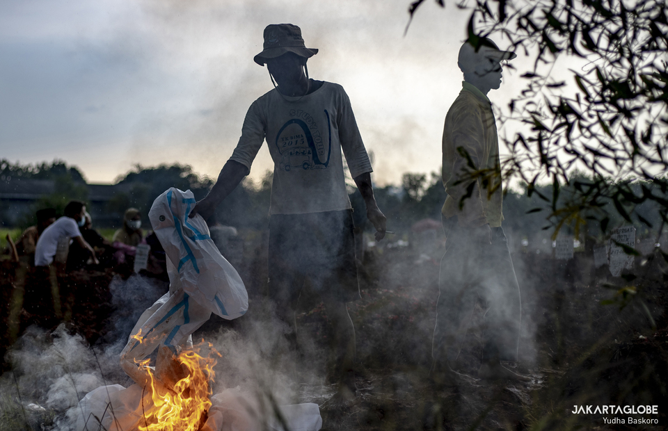 A funeral service worker burns used protective gear after the burial at Padurenan Cemetery in Bekasi, West Java on June 18, 2021. (JG Photo/Yudha Baskoro)