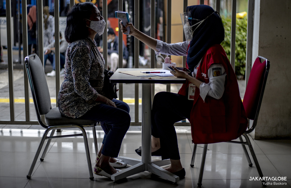 A commuterline passenger has her body temperature measured in Tanah Abang Station in Central Jakarta on June 21, 2021. (JG Photo/Yudha Baskoro)