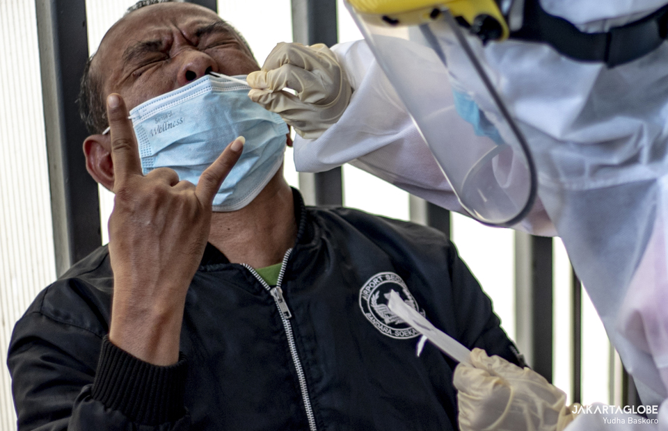 A man reacts as a health worker takes a swab sample from his nose at Tanah Abang Station in Central Jakarta on June 21, 2021. (JG Photo/Yudha Baskoro)