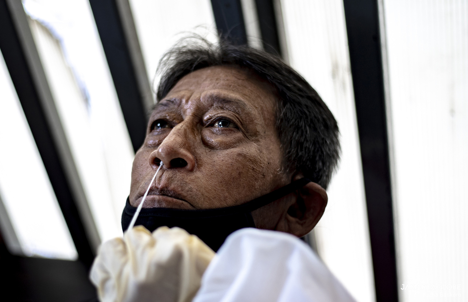 An old man reacts as health worker takes a swab sample from his nose at Tanah Abang Station in Central Jakarta on June 21, 2021. (JG Photo/Yudha Baskoro)
