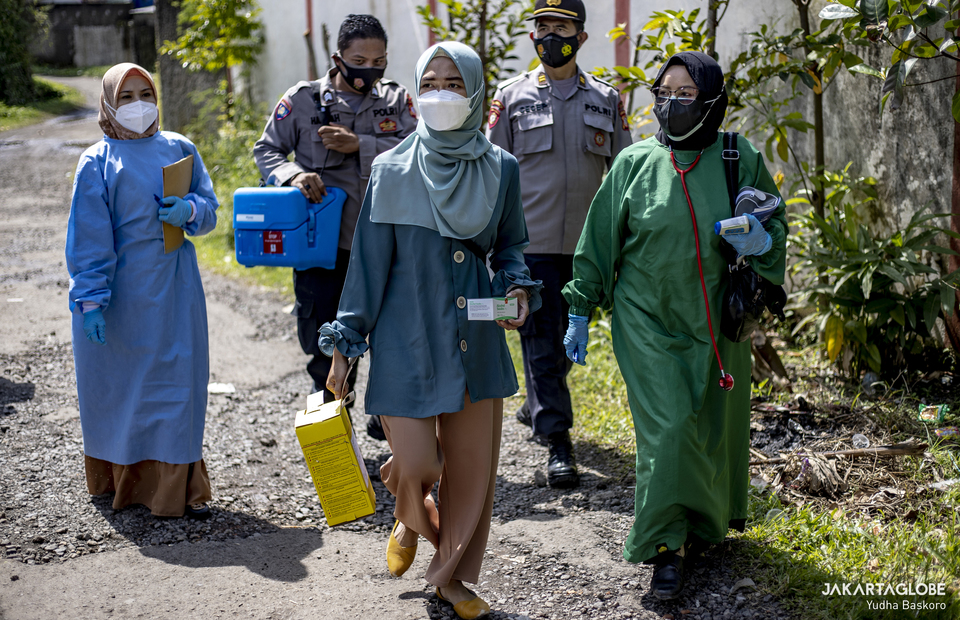 Pacet Subprecinct Police personnels and public health center workers walk as they want to carried out door to door COVID-19 vaccination programs in Cianjur regency, West Java on June 22, 2021. (JG Photo/Yudha Baskoro)