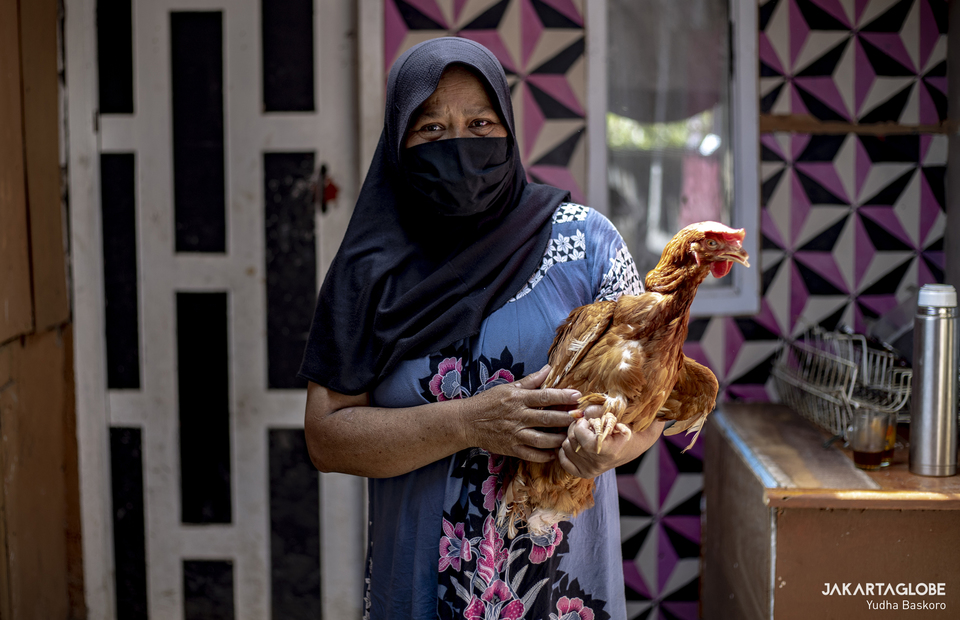 Ilmah, 61-year-old local poses for pictures while holding a live chicken rewarded after receiving his first dose of a COVID-19 vaccine, at his house in Cianjur regency, West Java province, Indonesia, June 22, 2021. (JG Photo/Yudha Baskoro)
