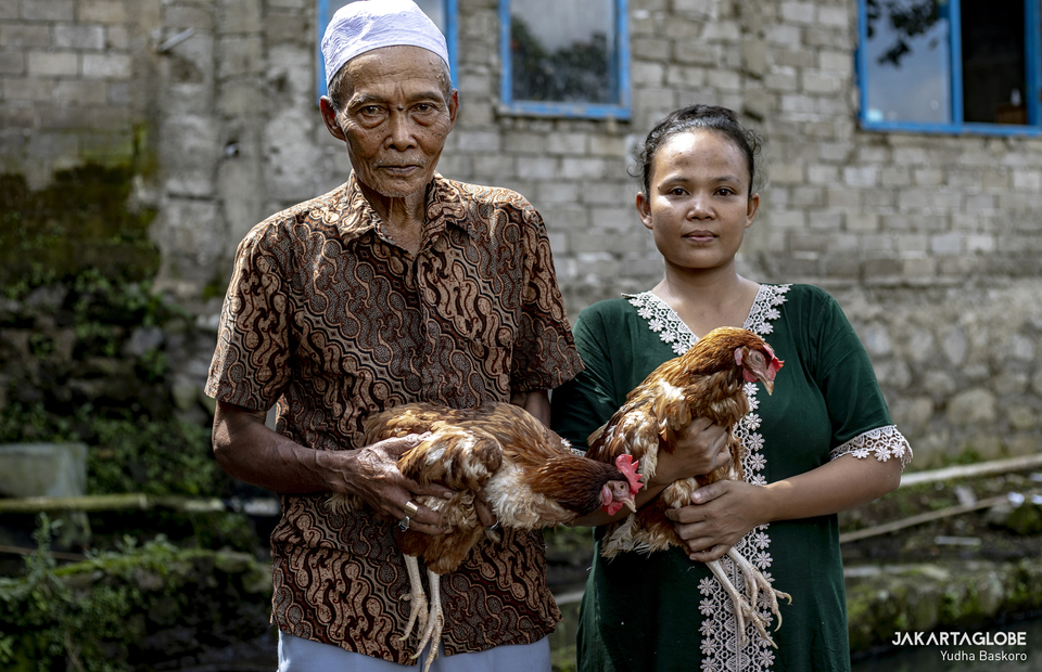 Badar, 74, and his daughter, Rohiman, 30, poses for pictures while holding a live chicken rewarded after receiving his first dose of a COVID-19 vaccine, at his house in Cianjur regency, West Java province, Indonesia, June 22, 2021. (JG Photo/Yudha Baskoro)