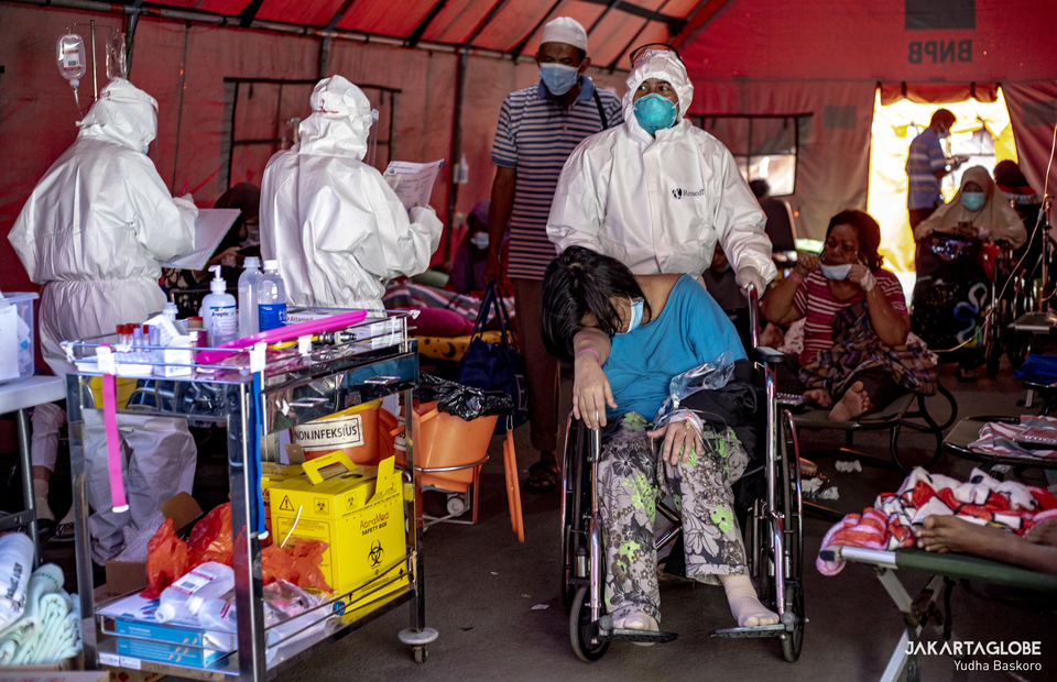 A health worker carries a patient inside a makeshift tent at Bekasi City Hospital in West Java on June 24, 2021. (JG Photo/Yudha Baskoro)