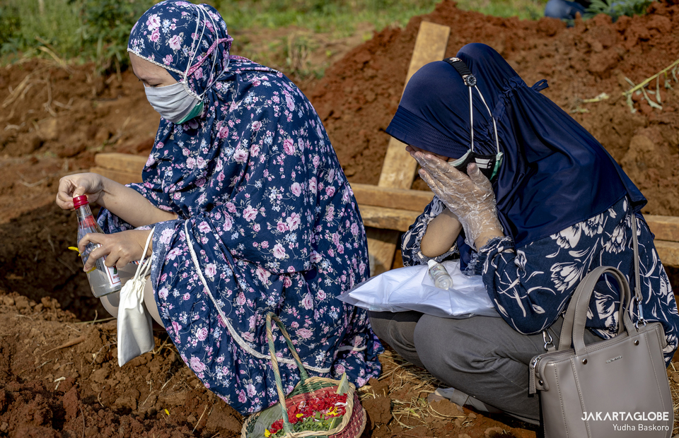 Family of the deceased pray next to the grave at Kayu Manis Cemetery in Bogor, West Java, on July 16, 2021. (JG Photo/Yudha Baskoro)